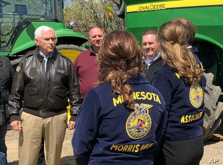Vice President Mike Pence, left, visits with farmers and future farmers as he tours the R & J Johnson Farms in Glyndon, Minn., May 9, 2019, to talk about the Trump administration's trade agreement with Canada and Mexico.