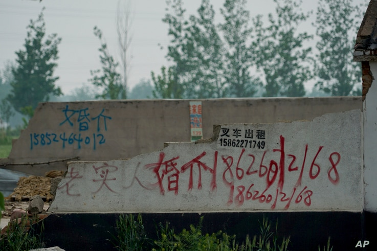 In this April 29, 2019 photo, graffiti advertising a marriage agent is spray-painted on the wall of a warehouse in Pei County in eastern China's Jiangsu province. In China, demand for foreign brides has mounted, a legacy of the one-child policy that ...
