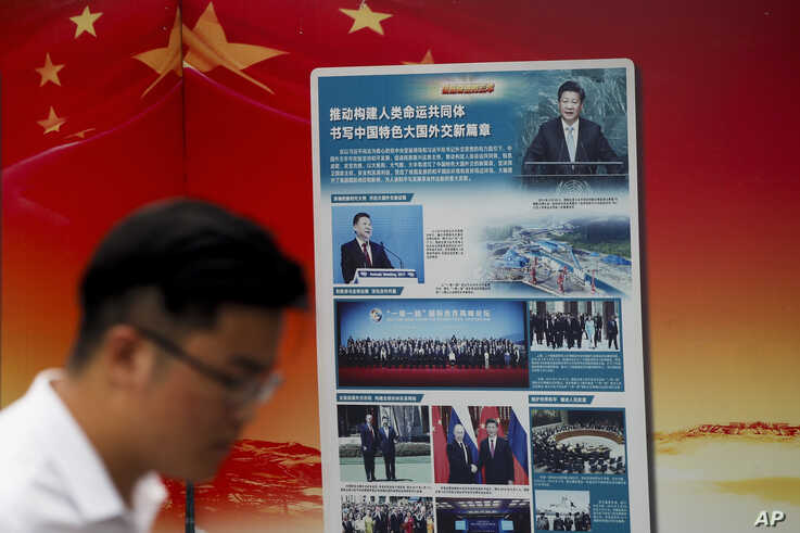 "FILE - A man walks by a government billboard promoting Chinese President Xi Jinping's signature ""Belt and Road"" initiative, outside a subway station in Beijing, China, Aug. 28, 2018."