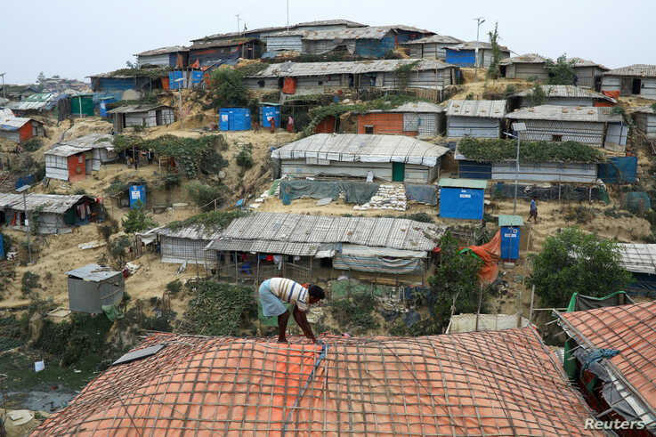 A Rohingya refugee repairs the roof of his shelter at the Balukhali refugee camp in Cox's Bazar, Bangladesh, March 5, 2019.