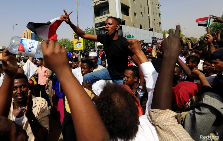 Sudanese demonstrators chant slogans as they protest against the army's announcement that President Omar al-Bashir would be replaced by a military-led transitional council, in Khartoum, April 11, 2019.