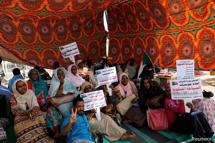 Sudanese protesters gather under a tent to protect themselves from the sun as they sit-in outside the defense ministry compound in Khartoum, Sudan, April 25, 2019.