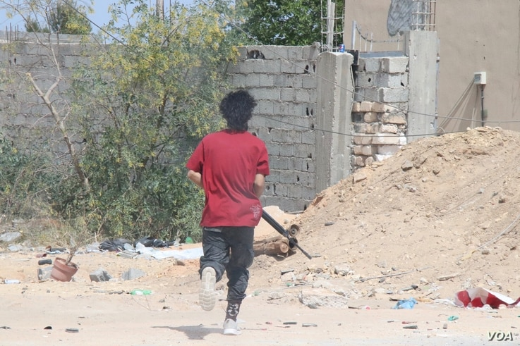A fighter with the western Government of National Accord's military runs to join a gun battle, May 1, 2019. in the suburbs of Tripoli in Libya.