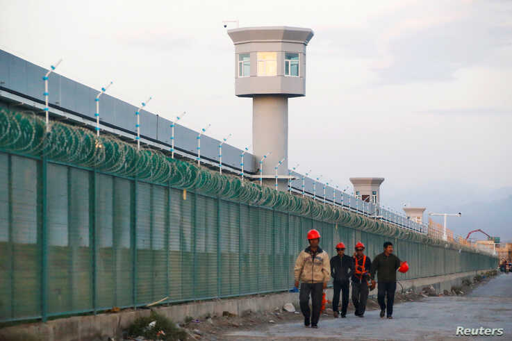 FILE PHOTO: Workers walk by the perimeter fence of what is officially known as a vocational skills education center in Dabancheng in Xinjiang Uighur Autonomous Region, China,Sept. 4, 2018.