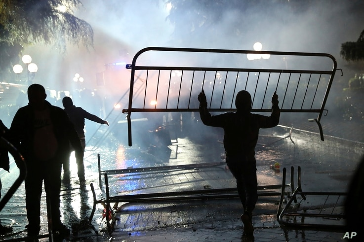 A protester removes a fence near the Parliament building during clashes with national police in Tirana, May 13, 2019.