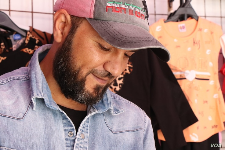 Sammy sells children's clothes in his stall in a market in Tripoli, Libya.  He says his alliance is with peace, not with any government, April 30, 2019.
