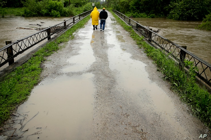Robert Collins, left, and Bobby Joe Branston watch rising waters in the Fishing River from a condemned bridge in Mosby, Missouri, May 21, 2019.