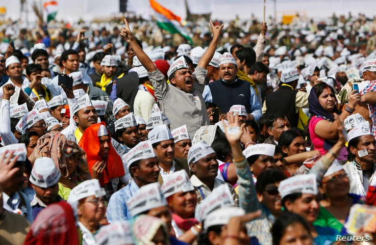 FILE - Supporters of Aam Aadmi Party (AAP) cheer after its chief, Arvind Kejriwal, took an oath as the new chief minister of Delhi in New Delhi, Feb. 14, 2015. The 2-year-old anti-graft party took office promising to fight divisive politics in a chal...