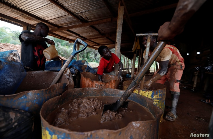 A young artisanal miner washes crushed rock containing gold in metal drums at the unlicensed mining site of Nsuaem Top in Ghana, Nov. 23, 2018.