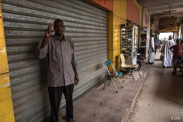 Siddig Ibrahim holds a V for Victory sign, a symbol of Sudan's revolution, outside his shuttered shop during the strike while one shop next door remains open, in Khartoum, Sudan, May 28, 2019.