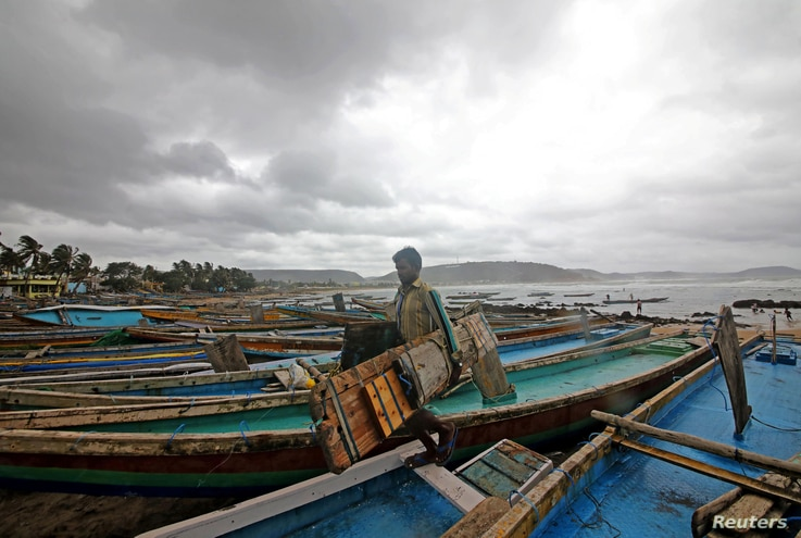 A fisherman carries his tools as he leaves for a safer place after tying his boats along the shore ahead of Cyclone Fani in Peda Jalaripeta on the outskirts of Visakhapatnam, India, May 1, 2019.