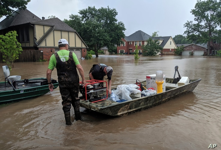 Brad and Bart Hindley take a boat to Brad's flooded house in Fort Smith, Ark., May 29, 2019. Brad said he doesn't live in a flood plain, but flood waters from the Arkansas River continue to rise.