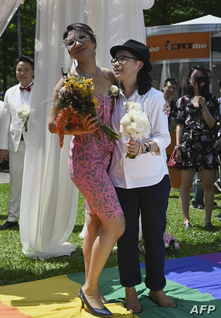 Gay couple Cynical Chick, left, and Li Ying-Chien display the wedding certificate at the Household Registration Office in Shinyi district in Taipei, May 24, 2019.