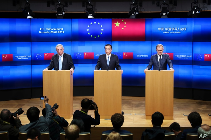 China's Premier Li Keqiang, center, talks to journalists during a joint news conference with European Council President Donald Tusk, right, and European Commission President Jean-Claude Juncker, left, during an EU-China summit at the European Council...