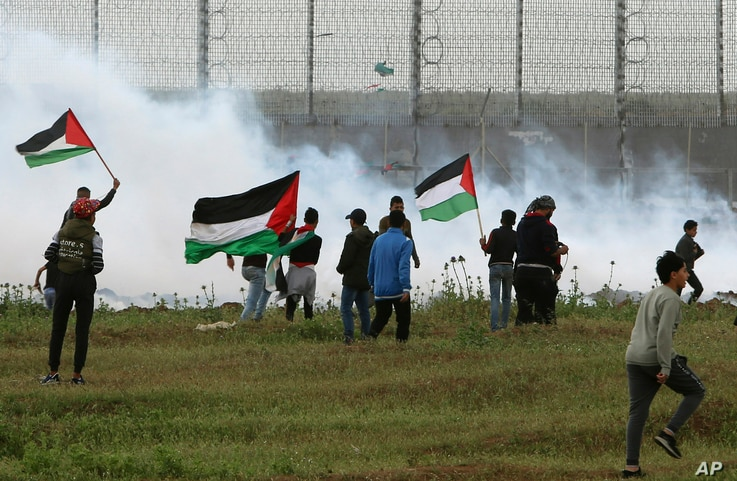 FILE - Protesters wave Palestinian flags amid teargas fired by Israeli troops near a fence on the Gaza Strip border with Israel, east of Gaza City, March 30, 2019.