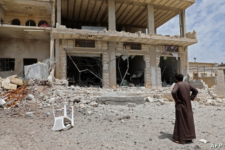 A man stares at a building damaged during reported shelling by government and allied forces, in the town of Hbeit in the southern countryside of the rebel-held Idlib province, Syria, May 3,2019.