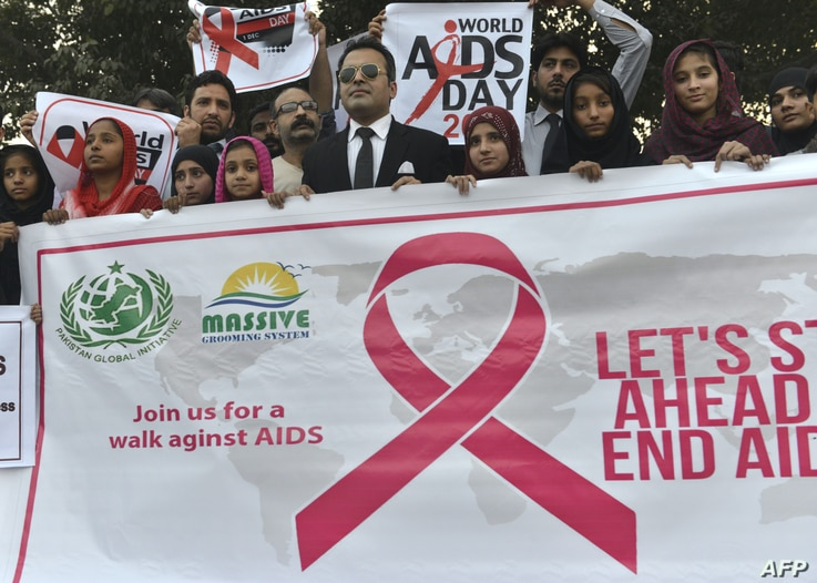 FILE - Pakistani social activists carry placards during a rally to raise awareness on World AIDS Day in Lahore, Dec. 1, 2016.