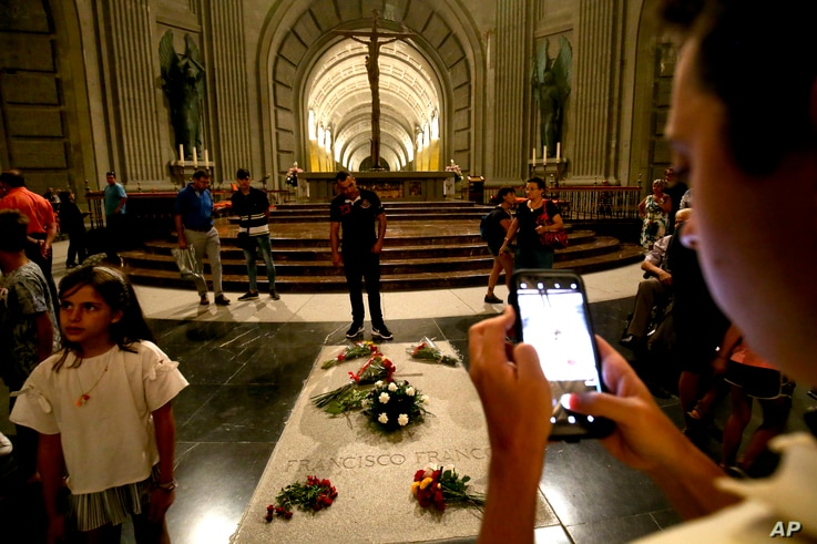 People stand around the tomb of former Spanish dictator Francisco Franco inside the basilica at the the Valley of the Fallen monument near El Escorial, outside Madrid, Aug. 24, 2018.