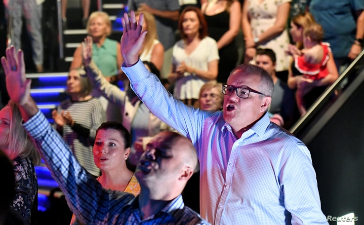 FILE - Prime Minister Scott Morrison and wife Jenny sing during an Easter Sunday service at his Horizon Church at Sutherland in Sydney, April 21, 2019. (AAP Image/Mick Tsikas/via Reuters)