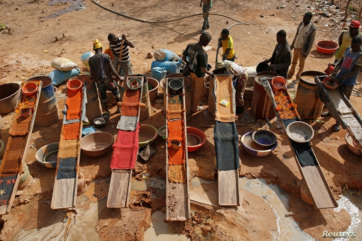Artisanal miners sluice for gold by pouring water through gravel at an unlicensed mine near the city of Doropo, Ivory Coast, Feb. 13, 2018.