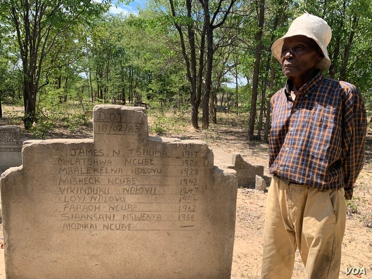 Melwa Ngwenya, stands in front of one of a shallow grave of victims of Zimbabwe's post-independence massacres in Tsholotsho district about 600 km southwest of Harare, April 18, 2019, where he son was buried by soldiers in February 1980. He says he ...