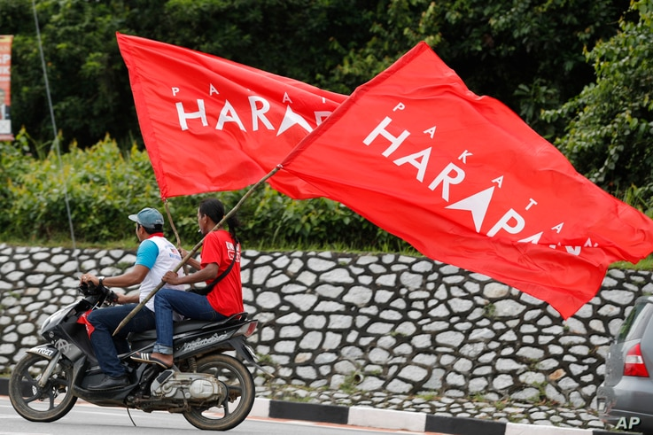 FILE - Supporters rides with flags of Pakatan Harapan (Alliance of Hope) in the southern coastal town of Port Dickson, Oct. 13, 2018.