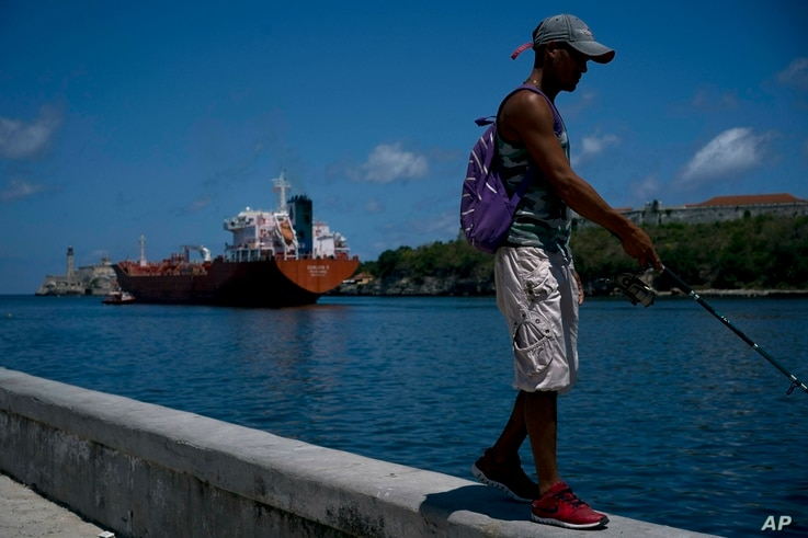 A fisherman walks on the Malecon seawall where an oil tanker can be see in the background in Havana, Cuba,  April 17, 2019. Washington has sanctioned Venezuela's oil industry and shipping companies that move Venezuelan oil to Cuba.