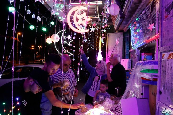 Palestinians check a shop selling Ramadan lights in the old city of Jerusalem, May 4, 2019, as Muslims around the world prepare for the announcement of the fasting month of Ramadan which is expected to start on May 5 or 6 depending on the crescent mo...