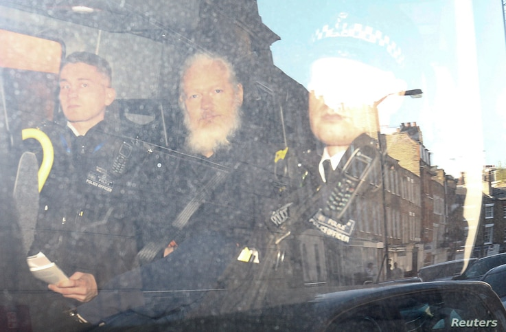 WikiLeaks founder Julian Assange (C) leaves the Westminster Magistrates Court in the police van, after he was arrested in London, Britain, April 11, 2019.