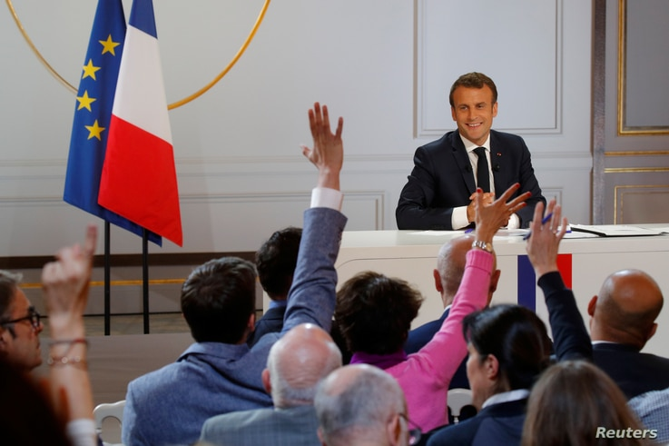 French President Emmanuel Macron reacts as journalists raise their hands to ask questions during a news conference to unveil his policy response to the yellow vests protest, at the Elysee Palace in Paris, April 25, 2019.
