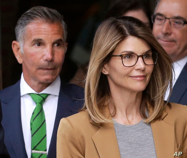 Actress Lori Loughlin, front, and husband, clothing designer Mossimo Giannulli, left, depart federal court in Boston after facing charges in a nationwide college admissions bribery scandal, Apr. 3, 2019.