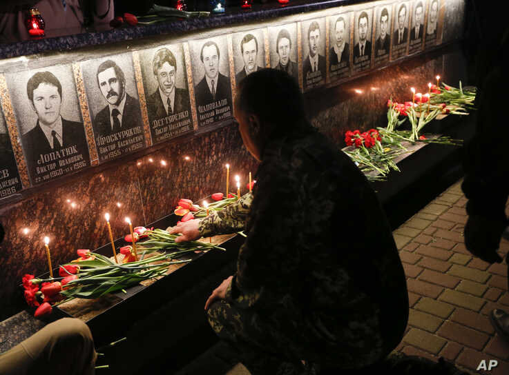 A Ukrainian lights candles to commemorate those who died after the Chernobyl nuclear disaster, during a ceremony at the memorial to Chernobyl firefighters.