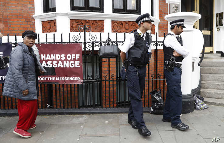 British police and protesters outside Ecuadorian Embassy in London
