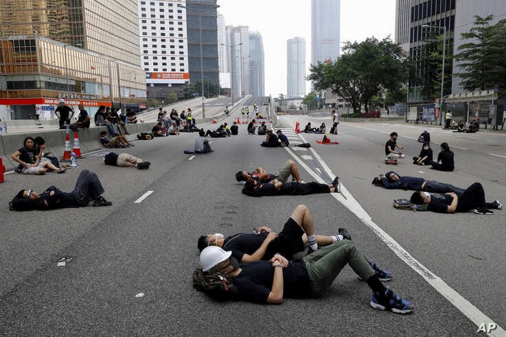 Protesters who camped out overnight take a rest along a main road near the Legislative Council after continuing protest against the unpopular extradition bill in Hong Kong, June 17, 2019.