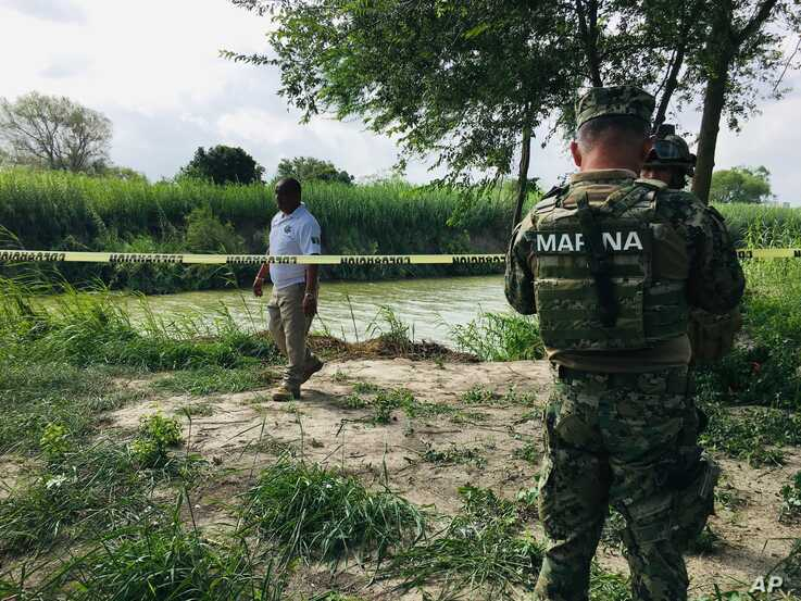 Mexican authorities walk along the Rio Grande bank where the bodies of Salvadoran migrant Oscar Alberto Martínez Ramírez and his nearly 2-year-old daughter Valeria were found, in Matamoros, Mexico, June 24, 2019.