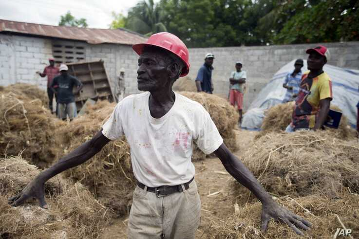 Clerme Elmacide stands amid bales of vetiver roots at a plant in Les Cayes, Haiti.