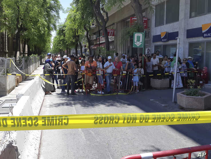 People are prevented to enter a security area after an explosion in Tunis, Thursday June 27, 2019.