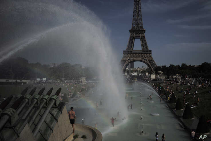 People cool off in the fountains of the Trocadero gardens, in front of the Eiffel Tower, in Paris, Friday, June 28, 2019.