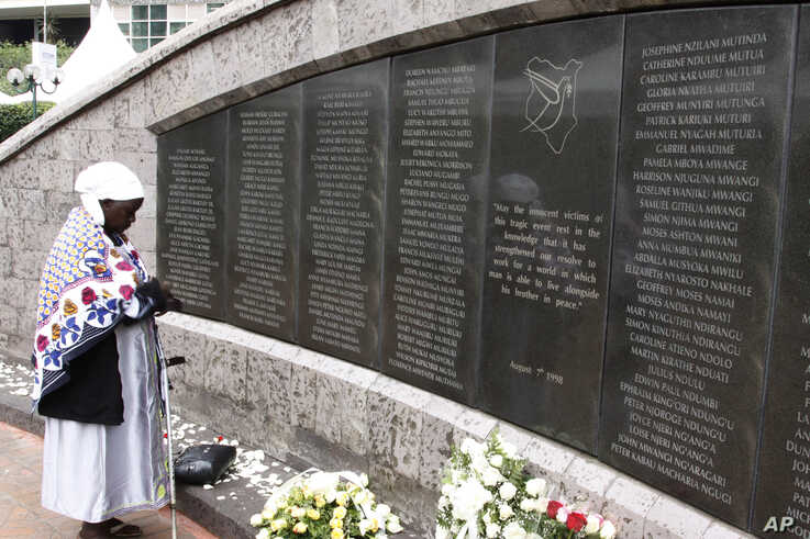 FILE - A woman prays for the victims at the memorial site in Nairobi, Kenya, Aug. 7, 2013 during events marking the 15th anniversary of the bombing of the U.S. Embassy in the city.