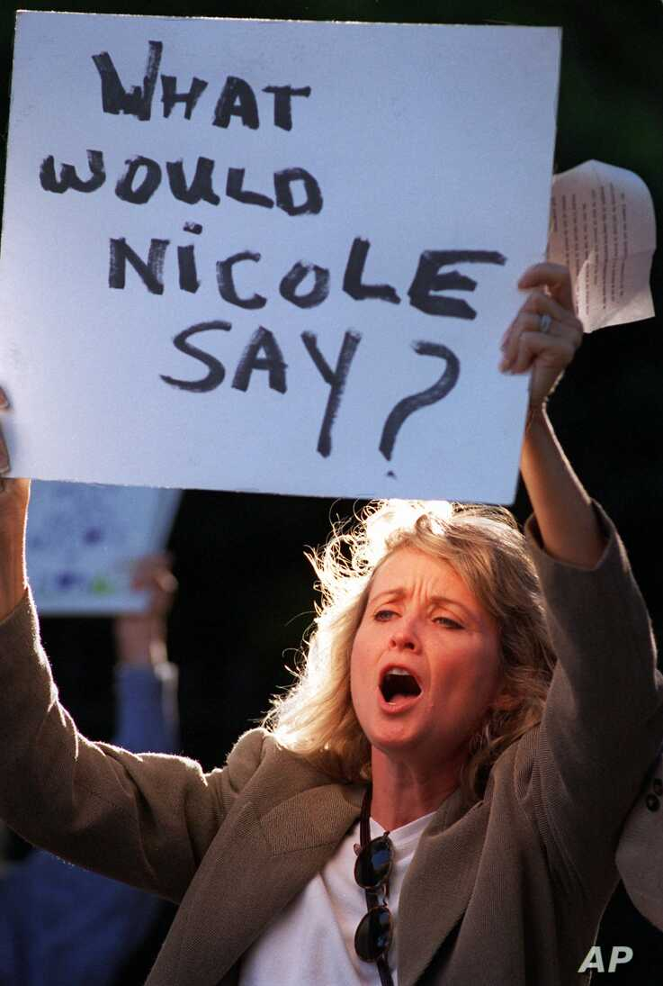 Protester Laurette Spang-McCook shouts at attendees of a fundraiser for the victims of domestic violence at the O.J. Simpson estate in Los Angeles, June 27, 1996.