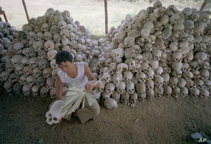 FILE - A man cleans a skull near a mass grave at the Chaung Ek torture camp run by the Khmer Rouge in this undated photo.