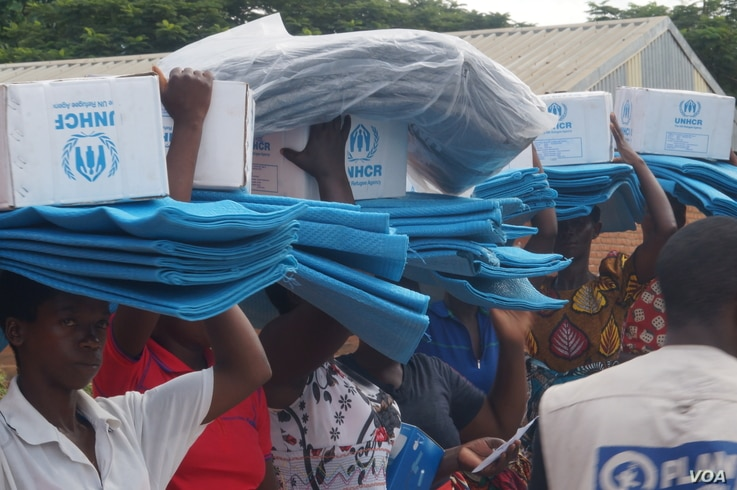 Flood survivors in Phalombe district, Malawi, carry relief items distributed by the UNHCR.