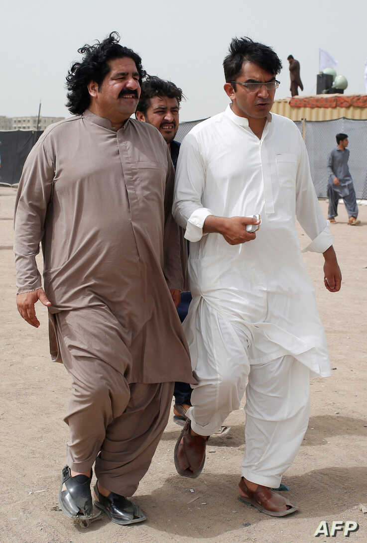 FILE PHOTO: Ali Wazir, left, and Mohsin Dawar, leaders of the Pashtun Tahaffuz Movement (PTM) walk at the venue of a rally against, what they say, are human rights violations by security forces, in Karachi, Pakistan, May 13, 2018.