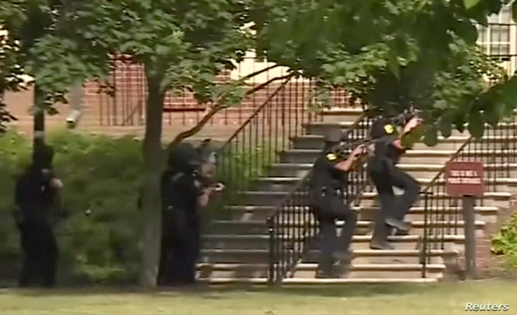 Police enter a building following a shooting at the municipal center in Virginia Beach, Va., May 31, 2019, in this still image taken from video.
