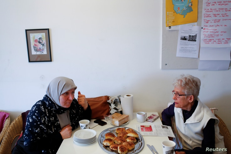Amnah Hamad, left, who is from Palestine and has lived in Denmark for 30 years, learns to speak Danish from teacher Anni Olsen who, as part of a group of seniors, volunteers to teach Danish to immigrants in Mjolnerparken, Copenhagen, Denmark, May 1, ...
