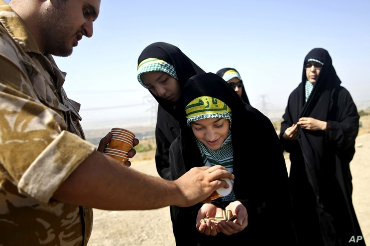 FILE-- In this Aug. 22, 2013 file photo, a female member of the Iranian Basij paramilitary militia, affiliated to the Revolutionary Guard, receives bullets during a training session in Tehran, Iran.