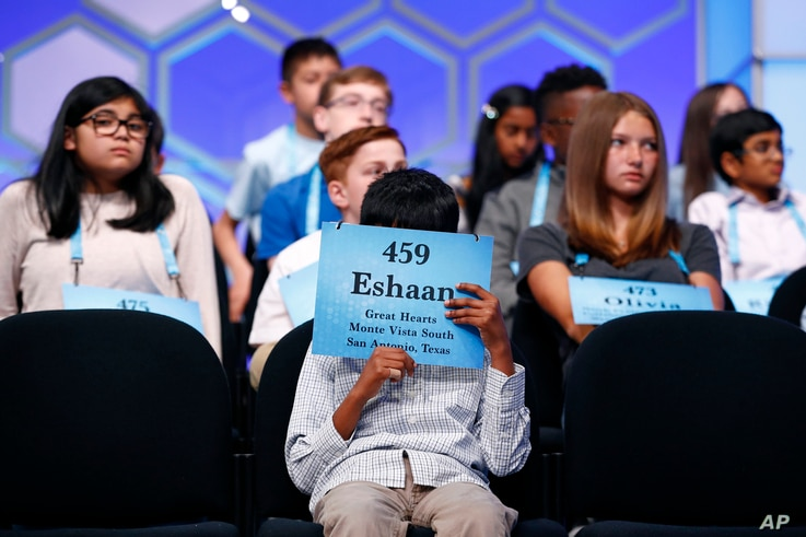Eshaan Sanka, 9, of Helotes, Texas, reads the back of his name tag in the third round of the Scripps National Spelling Bee, Wednesday, May 29, 2019, in Oxon Hill, Md.