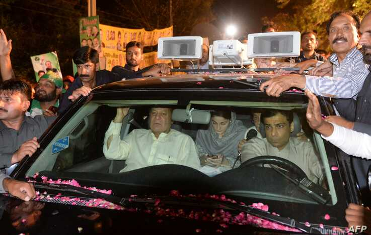 Former Pakistani Prime Minister Nawaz Sharif, center left, sits in a car as he heads back to Kot Lakpat Jail in Lahore, May 7, 2019.