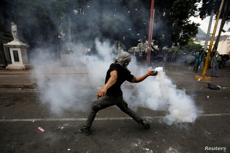 A demonstrator throws a gas canister back towards police officers during a protest against government plans to privatize health and education services, in Tegucigalpa, Honduras, April 29, 2019.