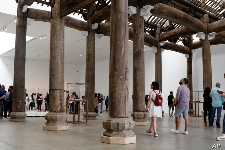 """People walk through a piece titled """"Ancestral Hall of the Wang Family,"""" part of an ancient Chinese construction rescued by Chinese concept artist and government critic Ai Weiwei, at the Contemporary Art University Museum in Mexico City, April 13, 201..."""
